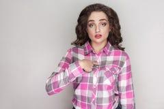 Είναι εγώ; Έκπληκτο όμορφο κορίτσι με το ρόδινο ελεγμένο πουκάμισο, $cu στοκ φωτογραφίες