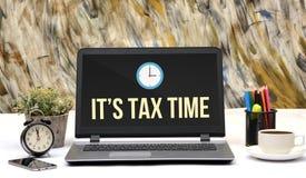 Είναι φορολογικός χρόνος με το εικονίδιο ρολογιών στην οθόνη lap-top Στοκ Εικόνα