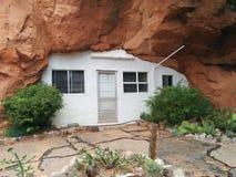 Είσοδος στην τρύπα Ν ` το σπίτι βουνών βράχου με τις ζωηρές πράσινες εγκαταστάσεις στοκ φωτογραφίες