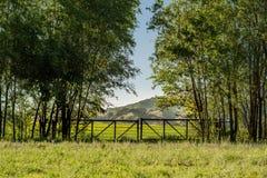 Είσοδος στον τομέα με την ξύλινη πύλη και βουνά στο υπόβαθρο Στοκ Εικόνες