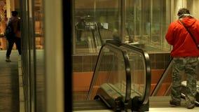 Είσοδος στο σταθμό μετρό με τις κυλιόμενες σκάλες, άτομο που πηγαίνει κάτω, δημόσιο μέσο μεταφοράς απόθεμα βίντεο