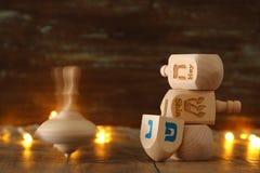 εβραϊκές διακοπές Hanukkah με την ξύλινα συλλογή & x28 dreidels περιστροφή top& x29  και χρυσά φω'τα γιρλαντών στον πίνακα Στοκ εικόνα με δικαίωμα ελεύθερης χρήσης