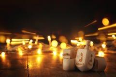 εβραϊκές διακοπές Hanukkah με την ξύλινα συλλογή & x28 dreidels περιστροφή top& x29  και χρυσά φω'τα στον πίνακα Στοκ Εικόνες