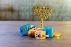 εβραϊκές διακοπές Hanukkah με τα ξύλινα dreidels νομίσματα κορυφών και σοκολάτας συλλογής περιστρεφόμενα στον πίνακα Στοκ Φωτογραφίες