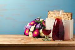 Εβραϊκή έννοια εορτασμού Pesah διακοπών Passover με το matzoh, το κρασί και τα λουλούδια πέρα από το μπλε αναδρομικό υπόβαθρο Στοκ Φωτογραφίες