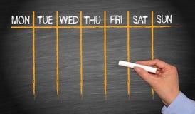Εβδομαδιαίο ημερολόγιο - θηλυκό χέρι με την κιμωλία που γράφει στον πίνακα στοκ φωτογραφία με δικαίωμα ελεύθερης χρήσης