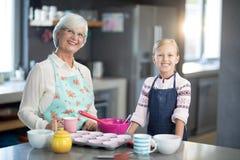Εγγονή και γιαγιά που θέτουν στεμένος στην κουζίνα στοκ φωτογραφία με δικαίωμα ελεύθερης χρήσης