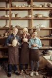 Εγγονή και παππούδες και γιαγιάδες που στέκονται και που κρατούν το βάζο και τα κύπελλα αργίλου ενάντια στον τοίχο Στοκ Φωτογραφία