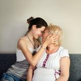 Εγγονή που αγκαλιάζει τη γιαγιά της και που πιέζει ενάντια στο FA της Στοκ Φωτογραφία