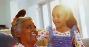 Εγγονή που βουρτσίζει την τρίχα γιαγιάδων της στο καθιστικό 4k απόθεμα βίντεο