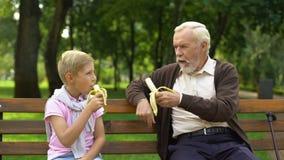 Εγγονός και granddad κατανάλωση των μπανανών στο πάρκο, οργανικά φρούτα, υγιής τρόπος ζωής απόθεμα βίντεο