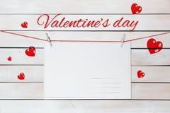 Εγγραφή και κάρτες ημέρας βαλεντίνου στα κόκκινα νήματα που περιβάλλονται από τις καρδιές στο ξύλινο άσπρο υπόβαθρο στοκ εικόνα