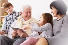 Εγγόνια και παππούδες και γιαγιάδες που χρησιμοποιούν μια ταμπλέτα Στοκ Εικόνες