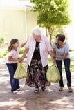 Εγγόνια που βοηθούν τη γιαγιά για να φέρει τις αγορές Στοκ Φωτογραφίες