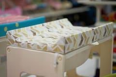 Εγκαθιστά το μεταβαλλόμενο στρώμα κρεβατιών επιτραπέζιων μωρών μαξιλαριών, αλλαγή πανών μωρών στοκ φωτογραφία με δικαίωμα ελεύθερης χρήσης