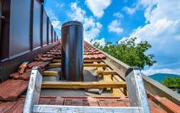 Εγκαθιστώντας την εξωτερική γούρνα καπνοδόχων μια στέγη σπιτιών με τα κεραμίδια στεγών Στοκ Φωτογραφία