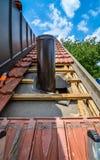 Εγκαθιστώντας την εξωτερική γούρνα καπνοδόχων μια στέγη σπιτιών με τα κεραμίδια στεγών Στοκ Φωτογραφίες
