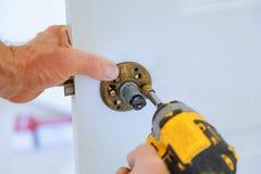 εγκατάσταση κλειδαριών ξυλουργών με το ηλεκτρικό τρυπάνι στην εσωτερική ξύλινη πόρτα στοκ εικόνα με δικαίωμα ελεύθερης χρήσης