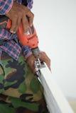 Εγκατάσταση πορτών Ο εργαζόμενος τρυπά μια τρύπα για το μπουλόνι της άρθρωσης με τρυπάνι Στοκ Εικόνα