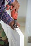 Εγκατάσταση πορτών Ο εργαζόμενος τρυπά μια τρύπα για το μπουλόνι της άρθρωσης με τρυπάνι Στοκ Εικόνες