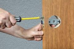 Εγκατάσταση της λαβής πορτών με το σύρτη, χέρια του κλειδαρά στενά στοκ εικόνες