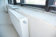 Εγκατάσταση της θέρμανσης θερμαντικών σωμάτων με τη θερμοστάτη στο ατελές κενό δωμάτιο στοκ φωτογραφία με δικαίωμα ελεύθερης χρήσης