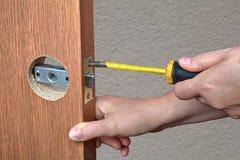 Εγκατάσταση της κλειδαριάς πορτών, μια κινηματογράφηση σε πρώτο πλάνο χεριών κλειδαράδων Στοκ εικόνα με δικαίωμα ελεύθερης χρήσης