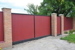 Εγκατάσταση της πύλης φρακτών τούβλου και μετάλλων με την πόρτα Κόκκινο μέταλλο Fenci στοκ φωτογραφία