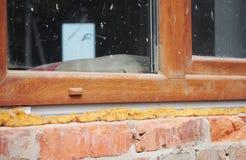 Εγκατάσταση του πλαστικού παραθύρου στο σπίτι τούβλου με τον αφρό καλαφατίζοντας πυροβόλων όπλων στοκ εικόνες