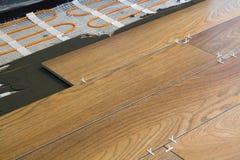 Εγκατάσταση των κεραμικών κεραμιδιών και των στοιχείων θέρμανσης στο θερμό πάτωμα κεραμιδιών Έννοια ανακαίνισης και βελτίωσης στοκ φωτογραφίες