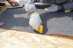 Εγκατάσταση των φεγγιτών στο νέο σπίτι Ο εργαζόμενος κτιστών κατασκευής συνδέει το υλικό μόνωσης στον προσανατολισμένο πίνακα σκε στοκ φωτογραφίες με δικαίωμα ελεύθερης χρήσης