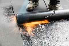 Εγκατάσταση υλικού κατασκευής σκεπής ρόλων με τη λυχνία συγκόλλησης προπανίου κατά τη διάρκεια του construc στοκ φωτογραφία με δικαίωμα ελεύθερης χρήσης
