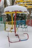 Εγκαταλειμμένα μη εργάσιμα ιπποδρόμια παιδιών ` s σε ένα λούνα παρκ που σκορπίζεται με το χιόνι φωτεινό ηλιόλουστο χειμερινό παγω Στοκ φωτογραφία με δικαίωμα ελεύθερης χρήσης