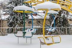 Εγκαταλειμμένα μη εργάσιμα ιπποδρόμια παιδιών ` s σε ένα λούνα παρκ που σκορπίζεται με το χιόνι φωτεινό ηλιόλουστο χειμερινό παγω Στοκ εικόνα με δικαίωμα ελεύθερης χρήσης