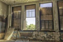 Εγκαταλειμμένη αίθουσα διδασκαλίας με τα μεγάλα παράθυρα στοκ εικόνες