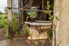 Εγκαταλειμμένη εκλεκτής ποιότητας παλαιά τουαλέτα έξω από την ακατάστατη αποθήκη - υγρός συμπυκνωμένος στοκ φωτογραφία