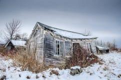 Εγκαταλειμμένη καμπίνα τουριστών στον τομέα με το χιόνι στοκ εικόνα