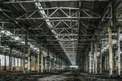 Εγκαταλειμμένη μεγάλη βιομηχανική αίθουσα ή αποθήκη εμπορευμάτων με τα απορρίματα, manufactory εργοστάσιο Στοκ Εικόνες