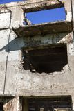 Εγκαταλειμμένος καταστρεμμένος από την έκρηξη, που βομβαρδίζει και που ξεφλουδίζει το κτήριο Τρύπες από τα κοχύλια, τα ίχνη σφαιρ στοκ εικόνες