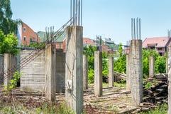 Εγκαταλειμμένο κτήριο ή ατελές εργοτάξιο οικοδομής σπιτιών με τις αρχιτεκτονικές λεπτομέρειες των συγκεκριμένων πόλων α σκελετών  Στοκ Εικόνες