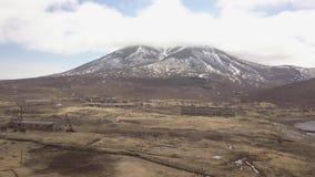 Εγκαταλειμμένο κτήριο στην πόλη στο βουνό με το χιονώδες εναέριο τοπίο αιχμών απόθεμα βίντεο