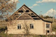 Εγκαταλειμμένο παλαιό παραδοσιακό σπίτι με ένα δέντρο στο μέτωπο σε ένα ουκρανικό χωριό Κλιμένοι τοίχοι, αγροτική ερήμωση στοκ εικόνες με δικαίωμα ελεύθερης χρήσης
