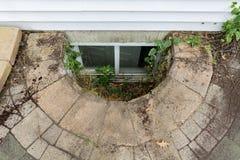 Εγκαταλειμμένο παράθυρο εξόδου σε ένα υπόγειο σπιτιών Στοκ Εικόνες