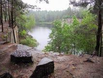 Εγκαταλειμμένο πλημμυρισμένο λατομείο στη δασική λίμνη στις δασικές  στοκ φωτογραφία με δικαίωμα ελεύθερης χρήσης