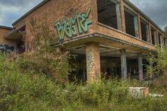 Εγκαταλειμμένο σχολείο που καλύπτεται στα γκράφιτι στοκ εικόνα