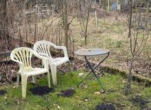 Εγκαταλελειμμένος κήπος με τις παλαιές ξεπερασμένες πλαστικό καρέκλες το χειμώνα στοκ εικόνες