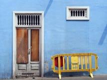 Εγκαταλελειμμένος που εγκαταλείπεται επιβιβασμένος επάνω στο μπλε σπίτι με την άσπρη σπασμένη πόρτα στοκ εικόνα