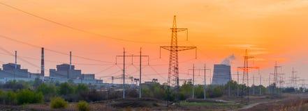 Εγκαταστάσεις παραγωγής ενέργειας στο ηλιοβασίλεμα με το νεφελώδη ουρανό Στοκ Εικόνες