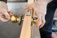 Εγκαταστήστε την εσωτερική πόρτα, ο ξυλουργός τοποθετεί το εξόγκωμα με την κλειδαριά, στενός-u χεριών στοκ εικόνα