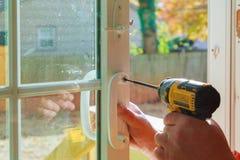 Εγκαταστήστε τη λαβή πορτών με μια κλειδαριά, ο ξυλουργός σφίγγει τη βίδα, χρησιμοποιώντας ένα ηλεκτρικό κατσαβίδι τρυπανιών στοκ φωτογραφία